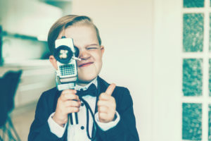 Boy with blond hair shows a thumbs up sign while shooting a video with an old analog 8 mm retro camera. The boy wears a tuxedo with a bow tie.
